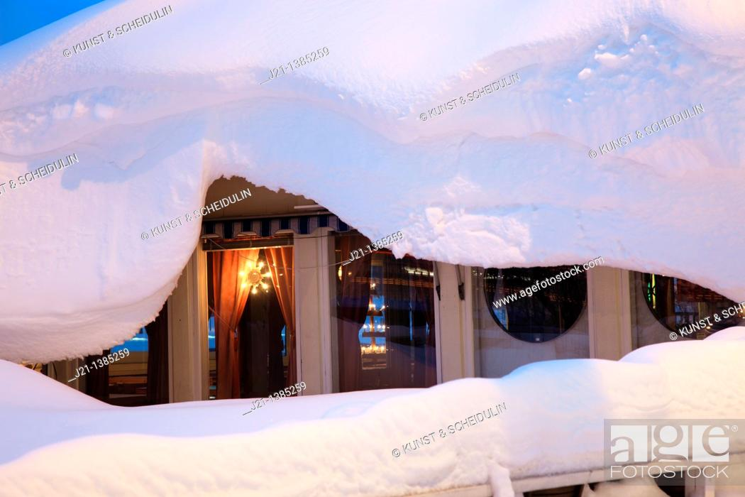 Stock Photo: Christmas lights glow in the window of a house covered with deep snow.
