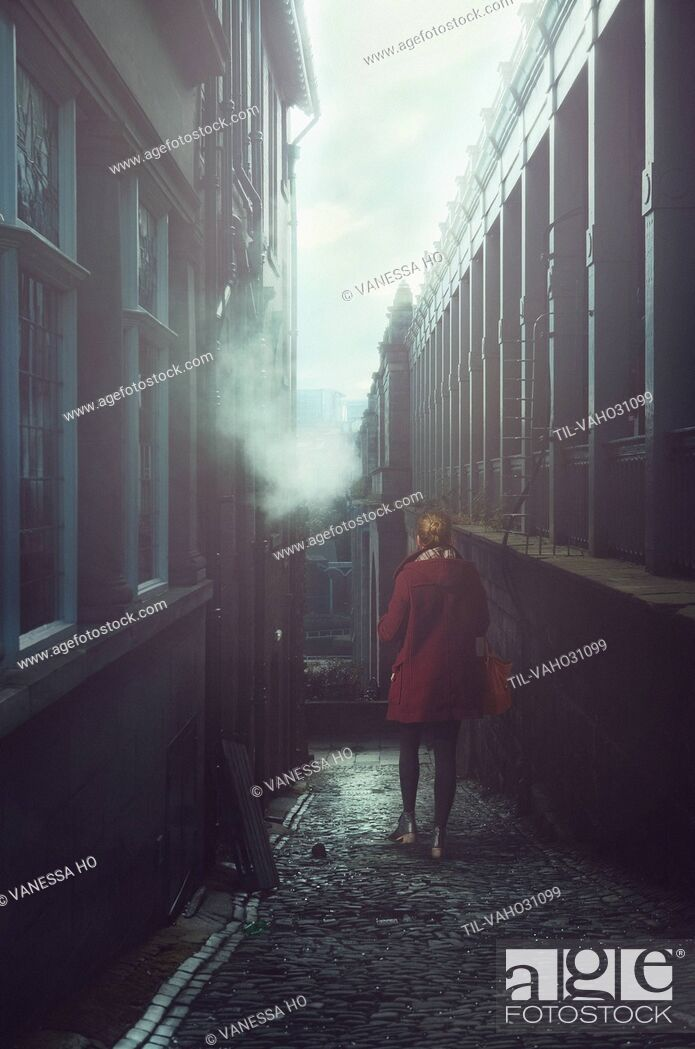 Stock Photo: young woman wearing red coat walking alone in street.