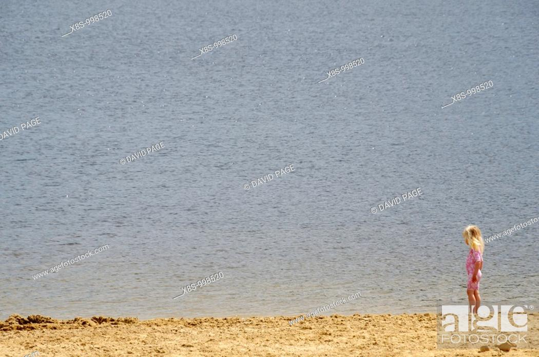 Stock Photo: Stock photo of a 3 year old girl standing alone by the side of the beach.