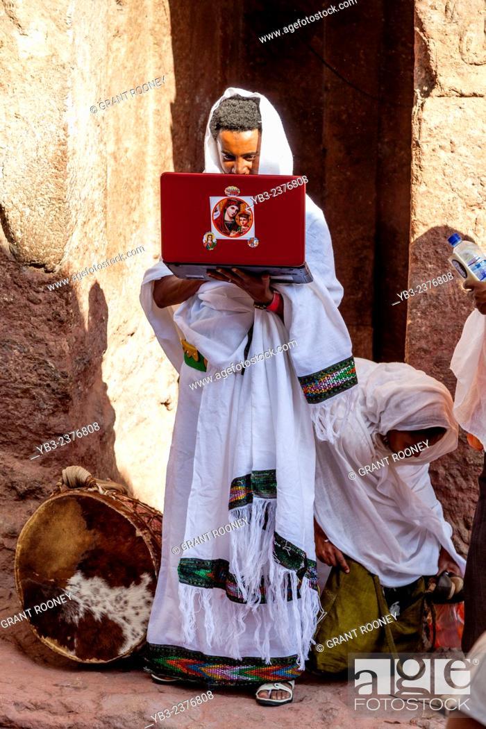 Stock Photo: A Christian Pilgrim Looking At A Laptop Computer Screen, Bete Maryam Church, Lalibela, Ethiopia.