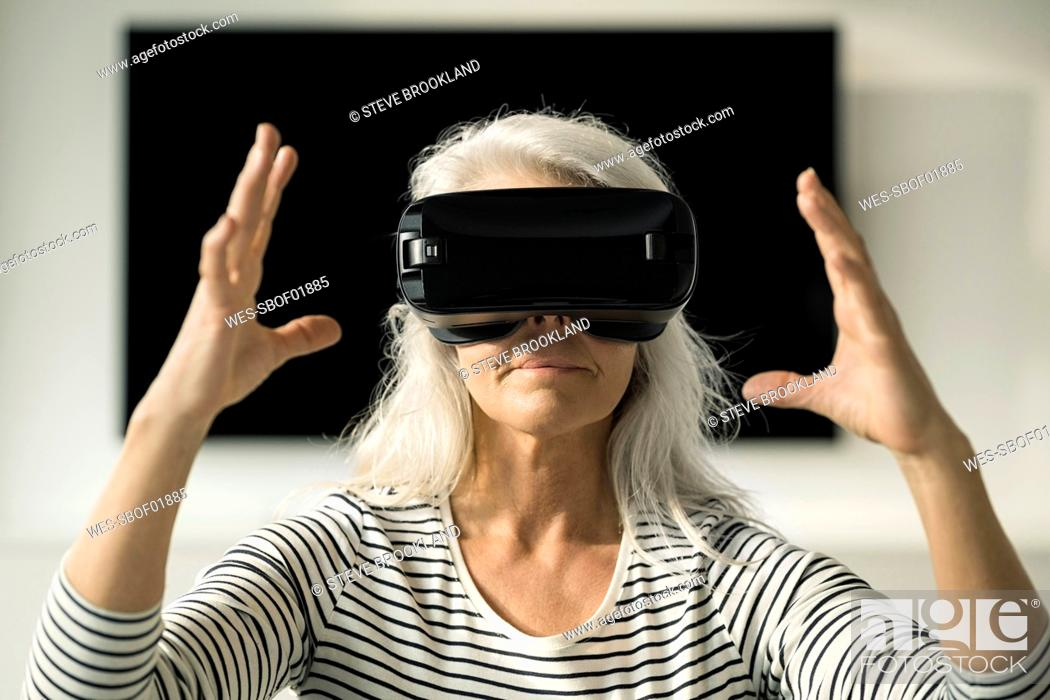 Stock Photo: Portrait of mature woman using Virtual Reality Glasses at home.