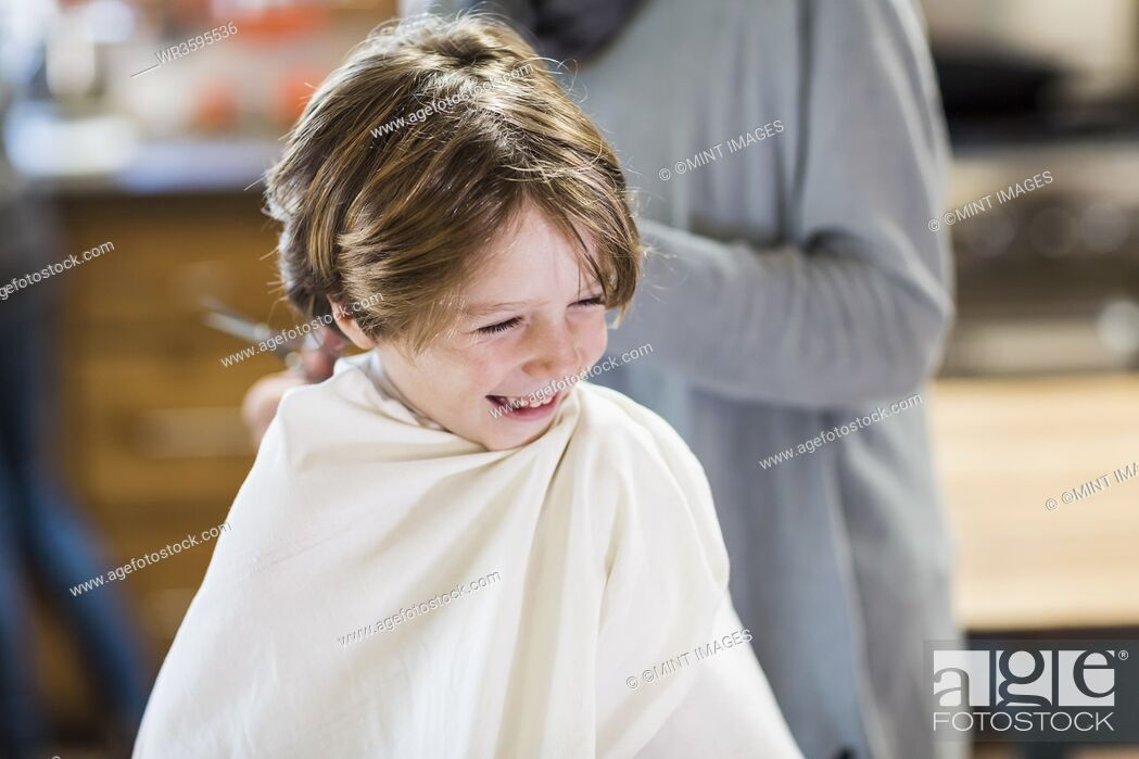 Stock Photo: A six year old boy getting his hair cut at home by his mother.