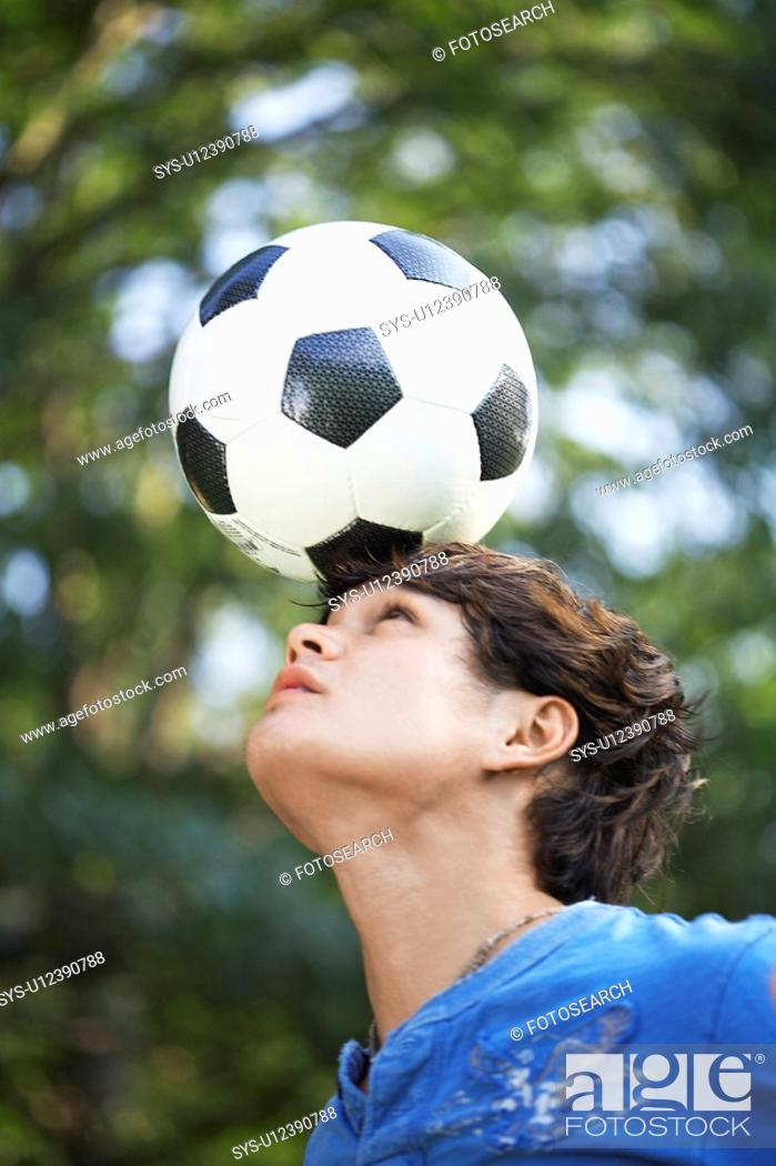 Stock Photo: Teenage boy balancing soccer ball on forehead.
