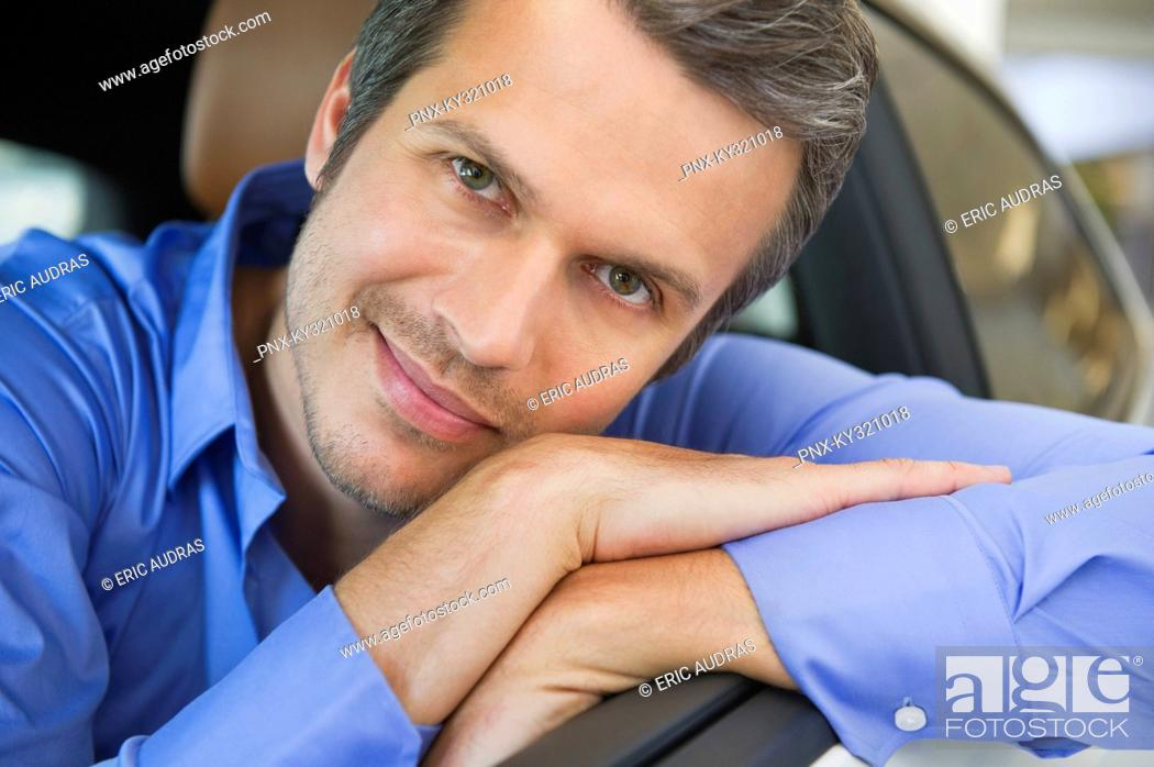 Stock Photo: Portrait of a happy mid adult man leaning on car window.