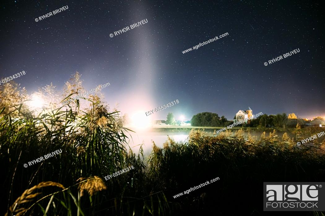 Imagen: Evaporation Over River Lake Near Houses In Village. Night Starry Sky Above Misty Lake River Landscape At Night. Glowing Stars Above Summer Nature.
