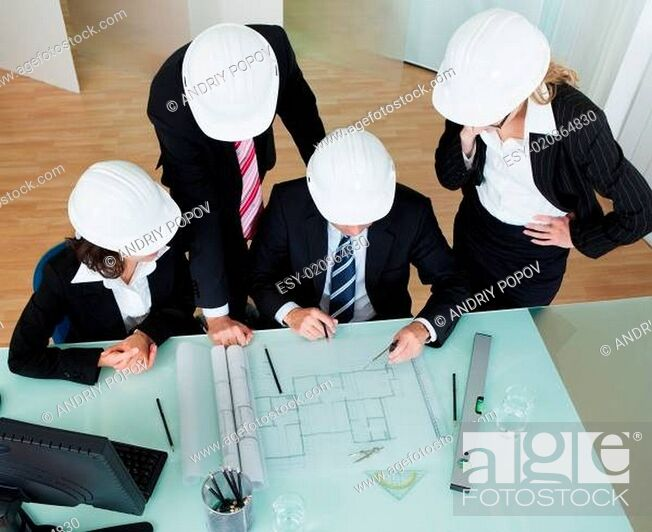 Stock Photo: Architects discussing a blueprint.