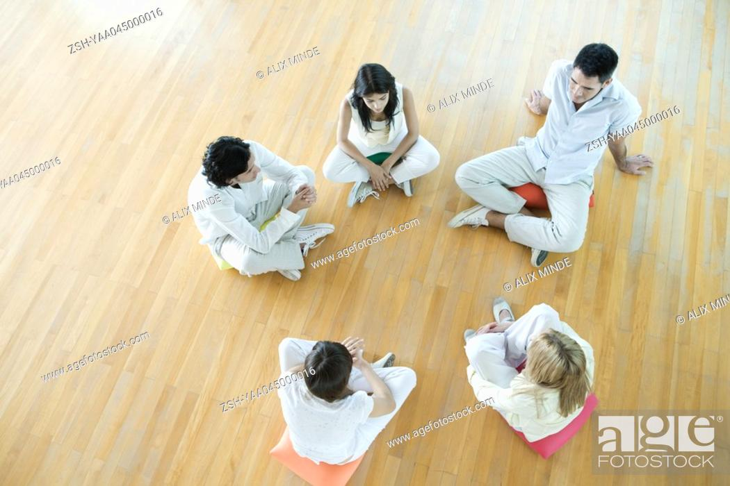 Stock Photo: Group therapy, adults sitting on floor in circle.
