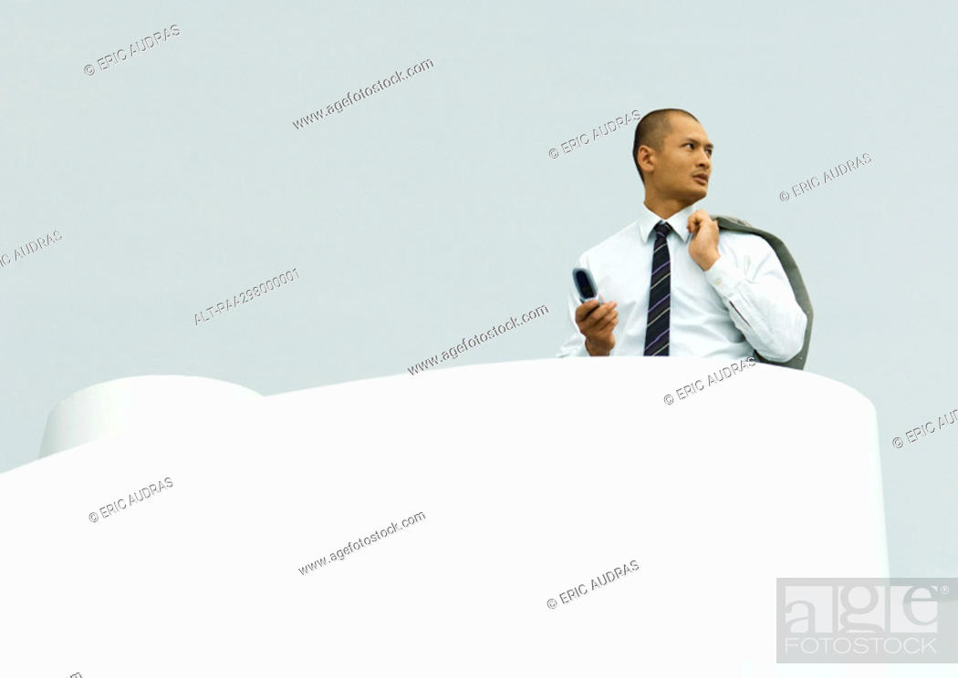 Stock Photo: Businessman holding cell phone in one hand and jacket over shoulder in the other.