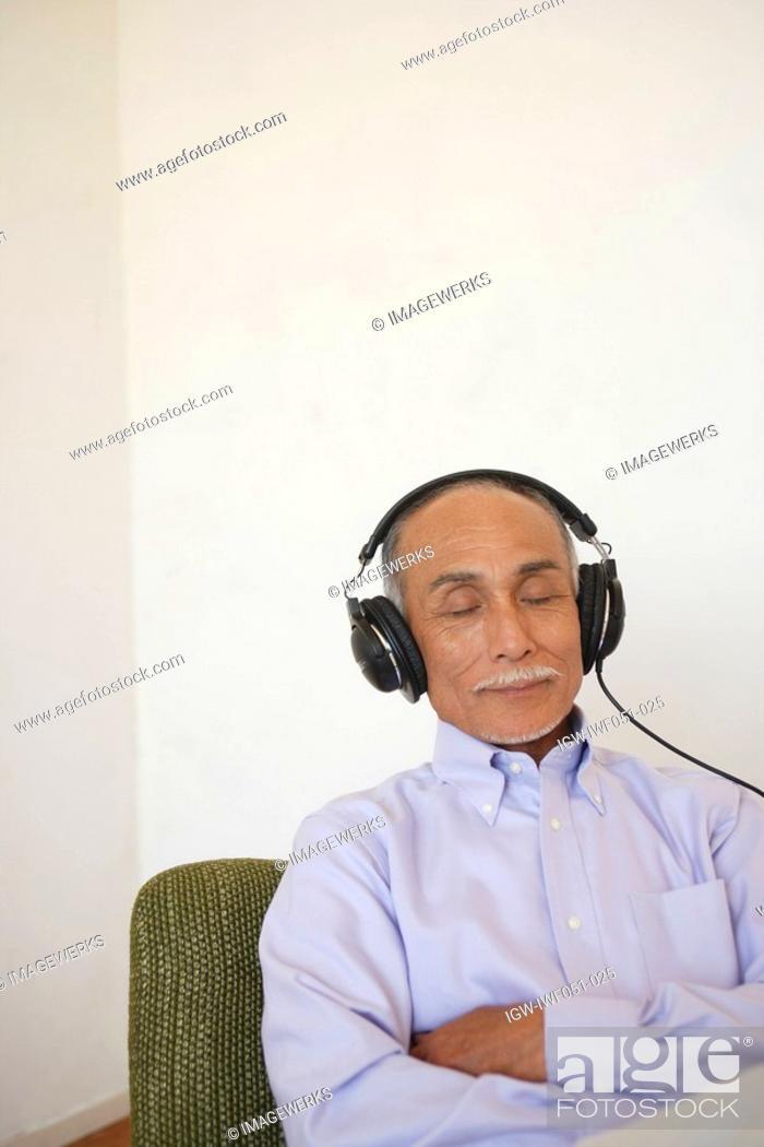 Stock Photo: Senior man listening music.