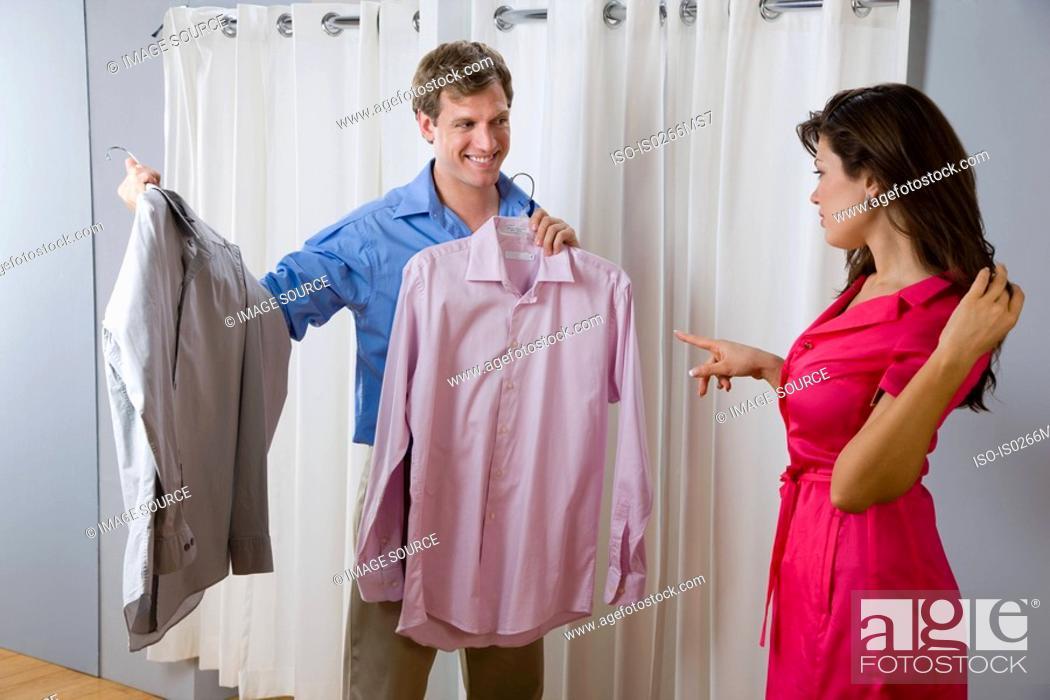 Stock Photo: A woman helping a man choose a shirt.