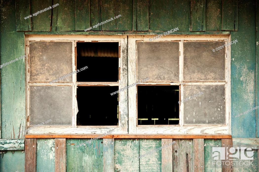 Stock Photo: Broken windows of derelect horse barn, California.