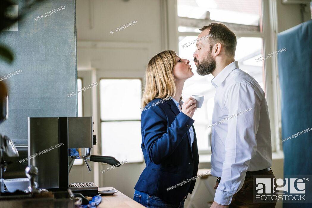 Stock Photo: Businessman kissing businesswoman in office.