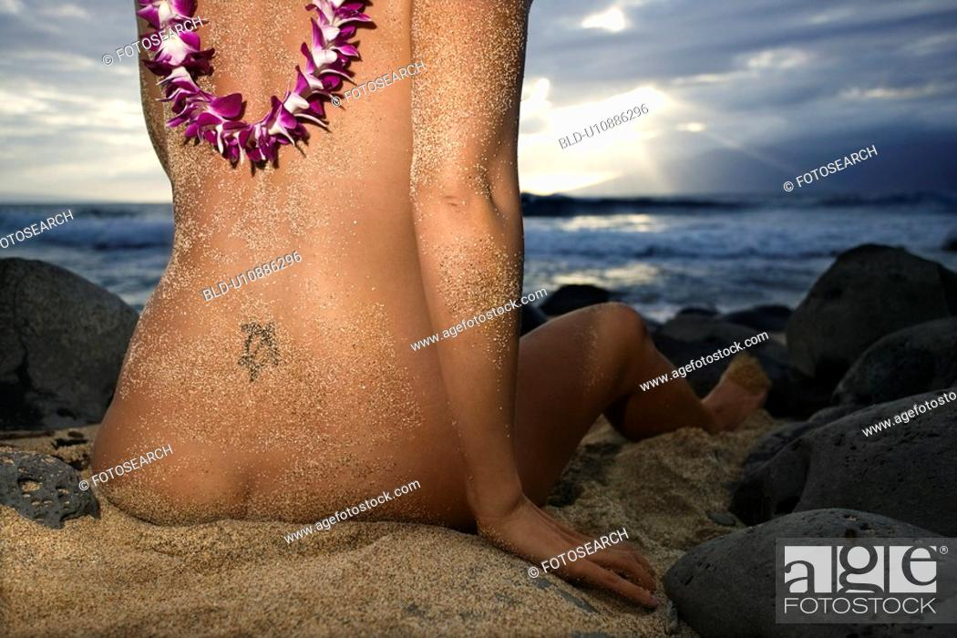 Stock Photo: Nude woman on beach sitting in sand.