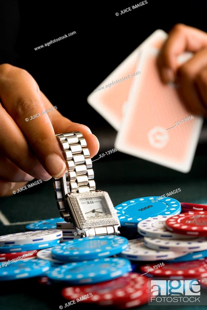 Stock Photo: Woman placing watch on pile of gambling chips on table, close-up.