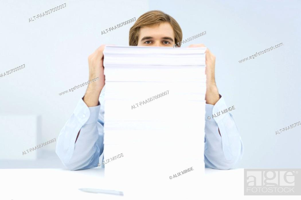 Stock Photo: Man peering over tall stack of paper.