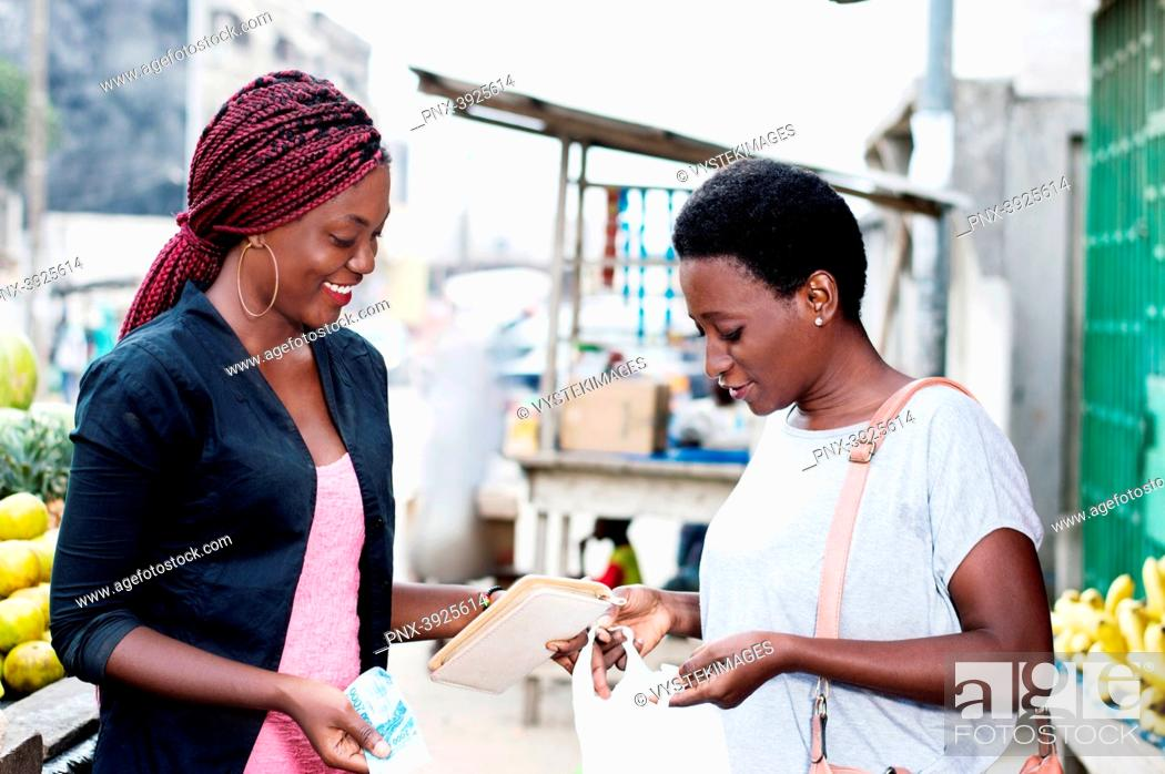 Stock Photo: Young happy women at the market looking in a bag containing fruit.