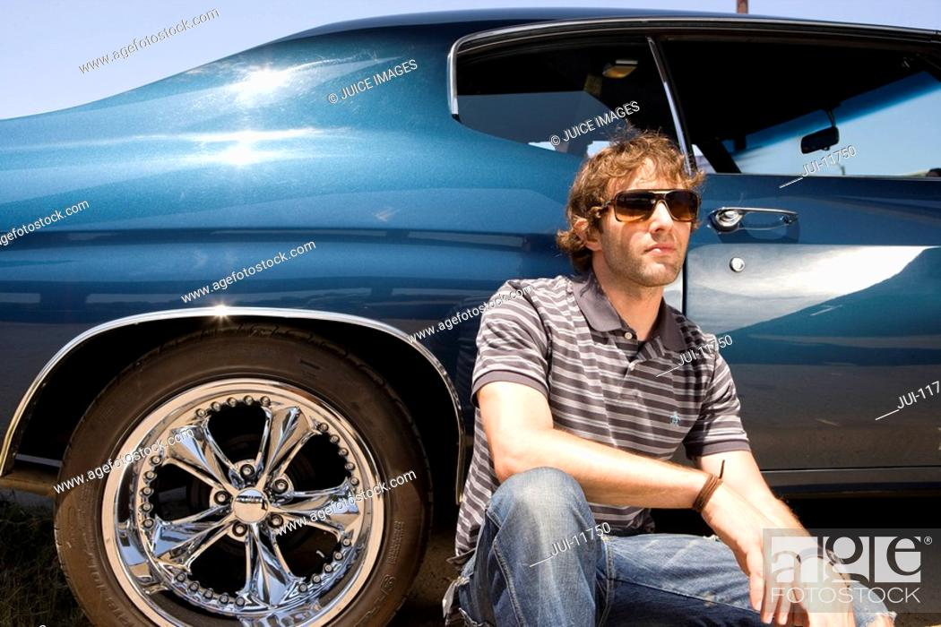 Stock Photo: Young man in sunglasses by car, close-up, low angle view.