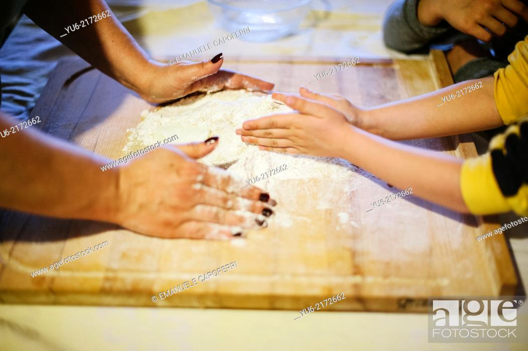 Stock Photo: Hands of mother and sons in the flour and mix the ingredients to make a cake.
