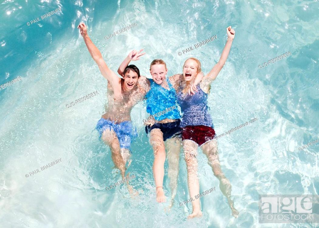 Stock Photo: Friends in swimming pool with arms raised.