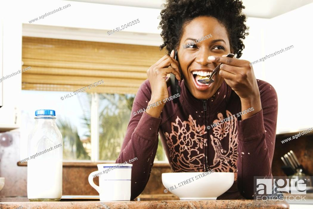 Stock Photo: African American woman eating cereal.