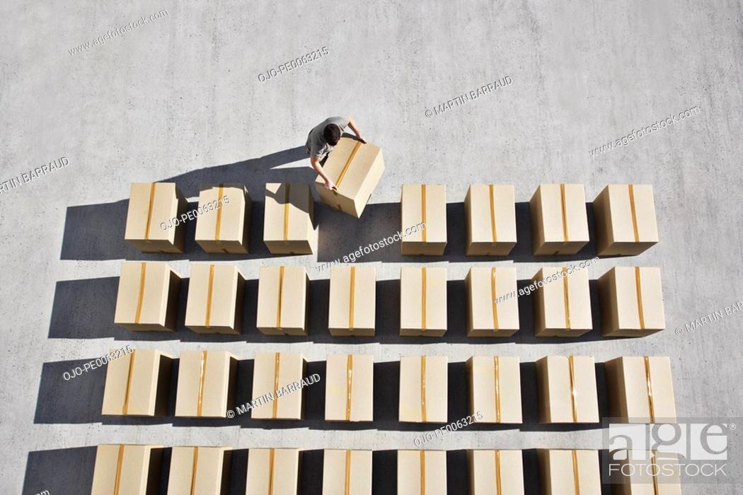 Stock Photo: Man placing box into line.