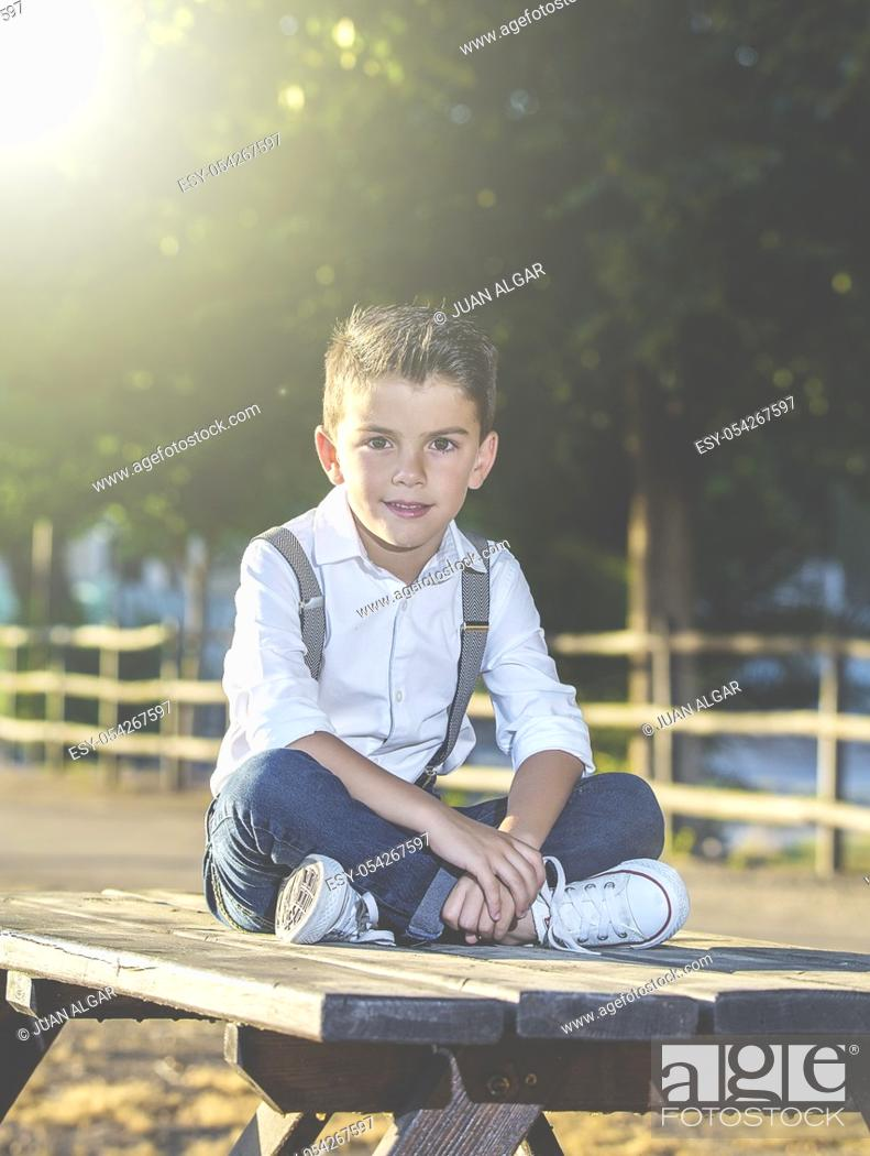 Stock Photo: Stylish boy in suspenders and jeans sitting on table in park looking at camera.