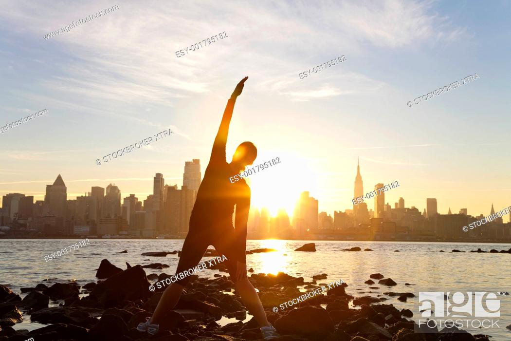 Stock Photo: A woman runner stretching in a yoga position in front of the Manhattan skyline, New York City, United States of America, at early morning dawn sunrise.