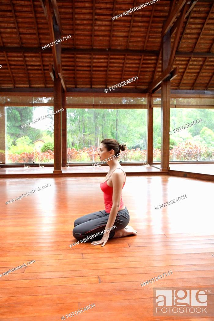 Stock Photo: Young woman in sports clothing sitting on wooden floor.