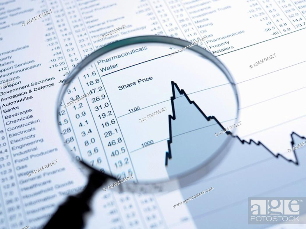 Stock Photo: Magnifying glass and descending line graph and list of share prices.