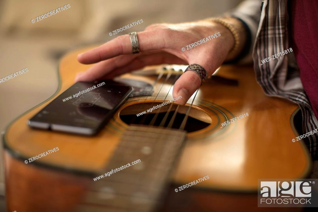 Imagen: Close-up of man's hand, cell phone and guitar.