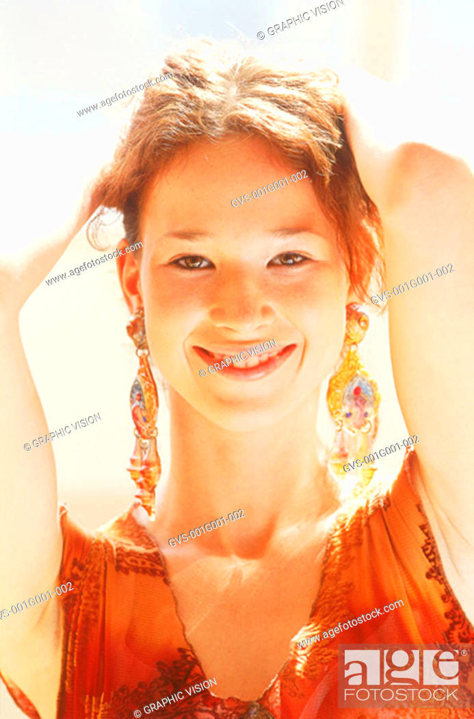 Stock Photo: Portrait of a Young Woman With Red Hair in Red Top with Hands Behind Head.