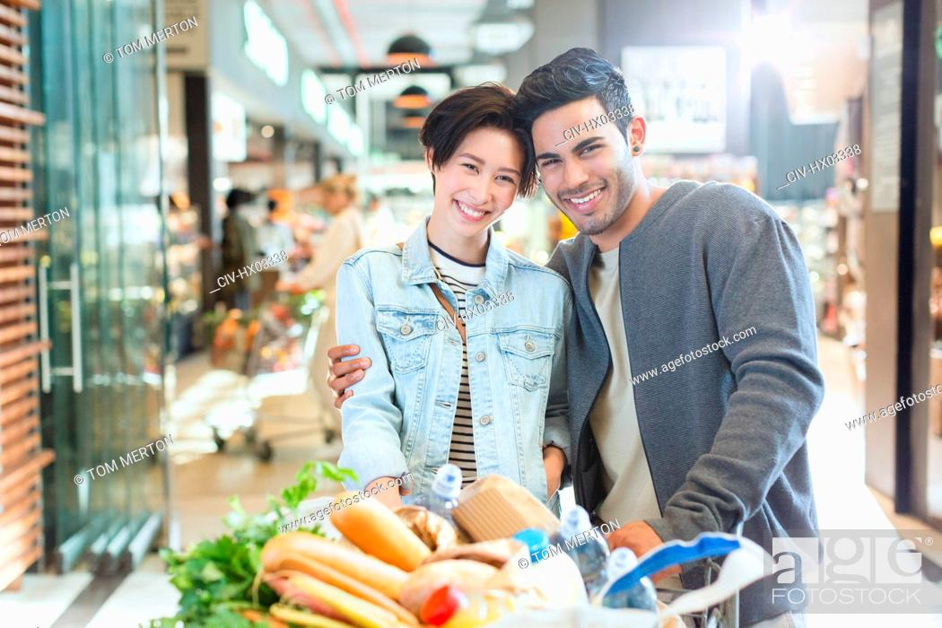 Stock Photo: Portrait smiling young couple grocery shopping in market.