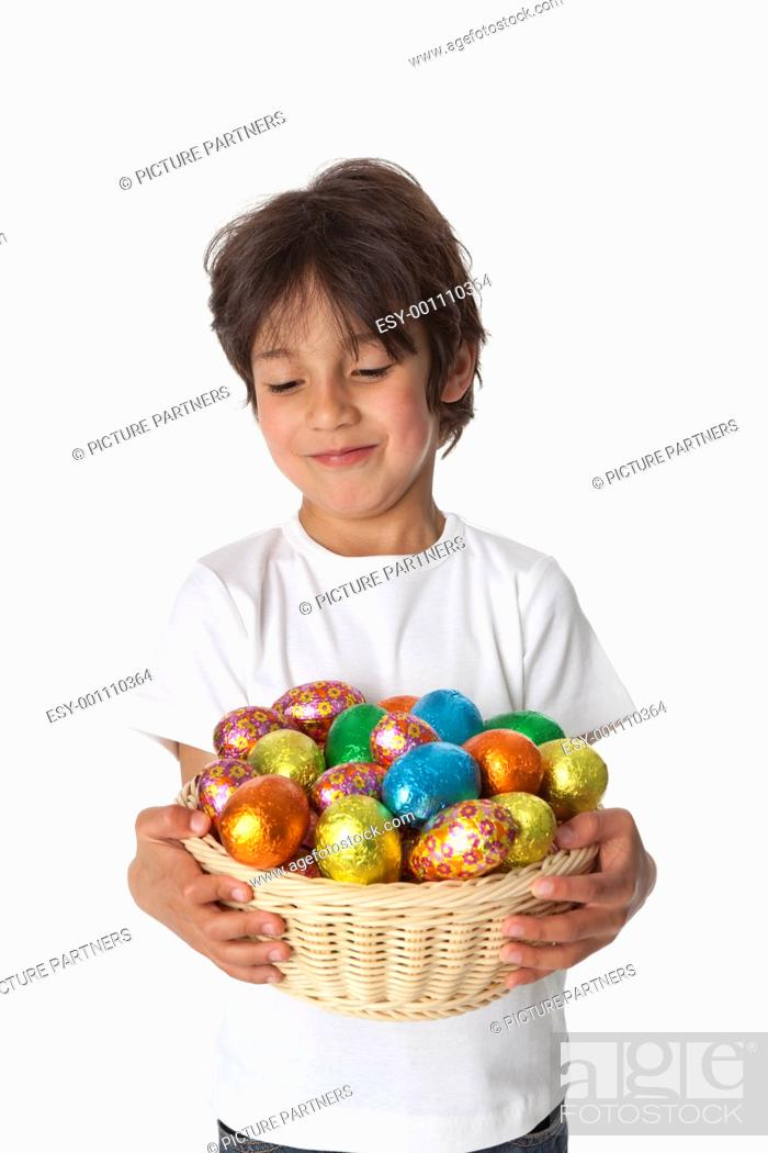 Stock Photo: Little boy with a basket of chocolate Easter eggs on white background.