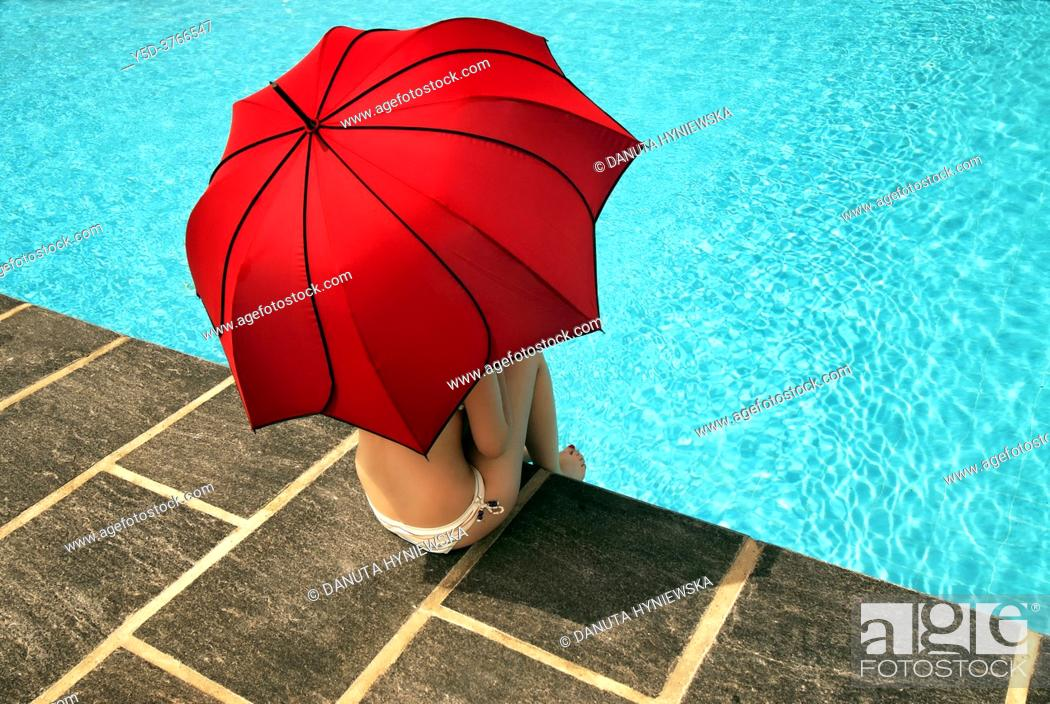 Imagen: young woman under red umbrella at poolside.