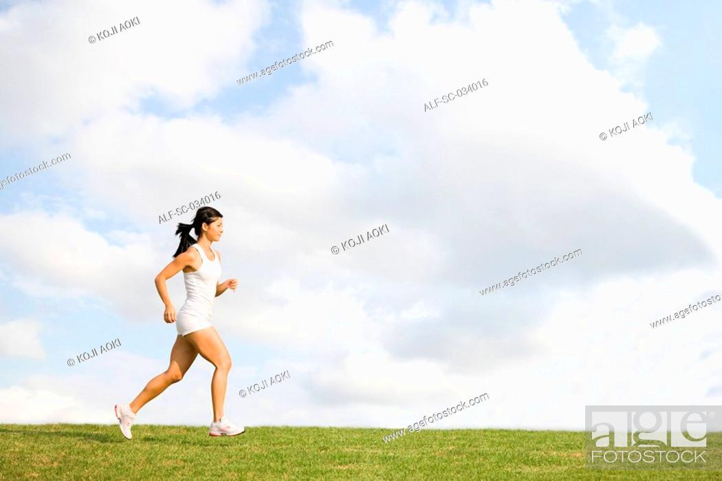 Stock Photo: Young Woman in tank top jogging on grass.
