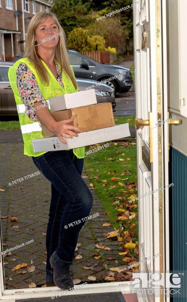 Stock Photo: Woman courier delivering packages to a front door of a customers home.