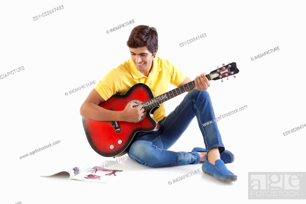 Stock Photo: Young man with a guitar looking at a book.