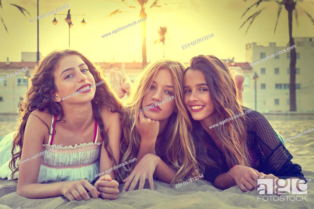 Stock Photo: Best friends girls at sunset beach sand smiling happy together filtered image.