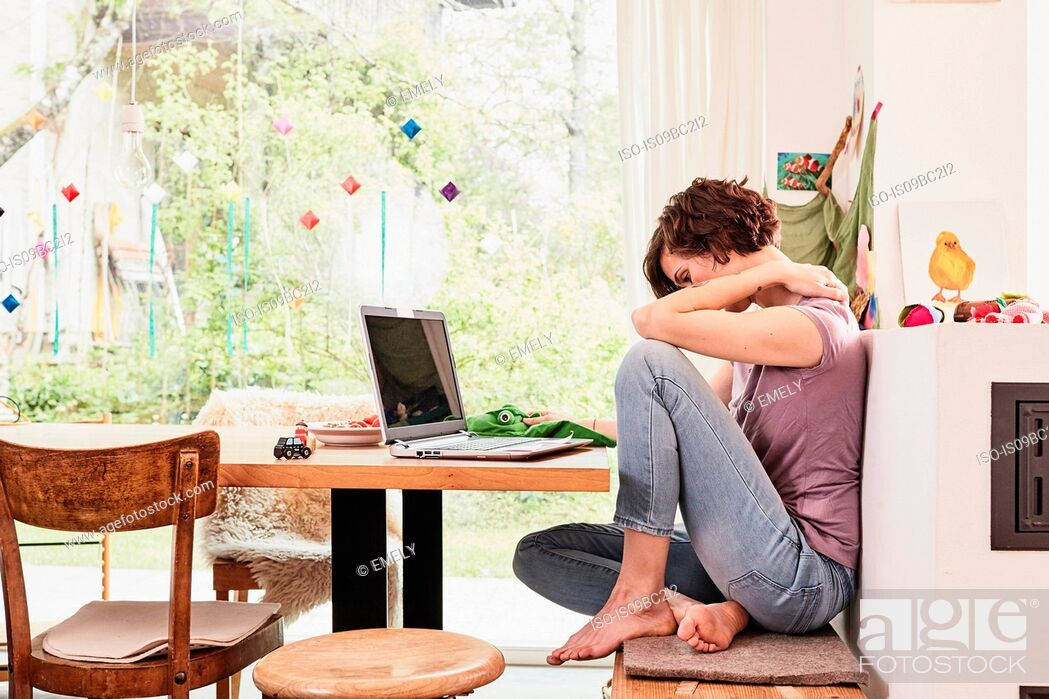 Stock Photo: Mid adult woman at home, using laptop, worried expression.