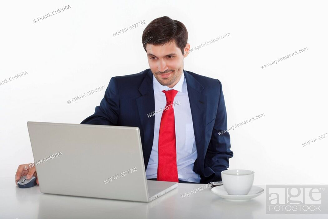 Stock Photo: Business executive in suit behind desk with laptop.
