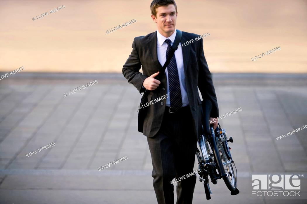 Stock Photo: A businessman carrying his folded bicycle to work.