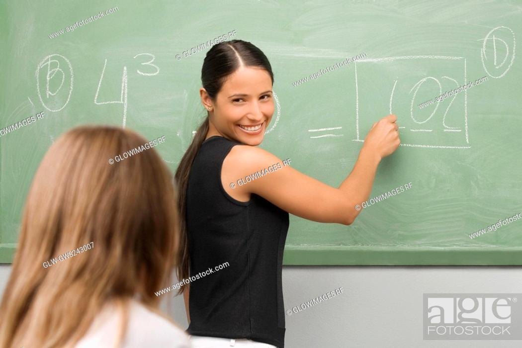 Stock Photo: Female teacher teaching a schoolgirl in a classroom and smiling.