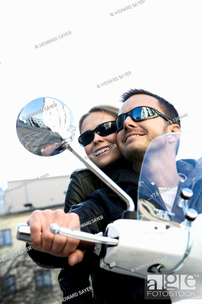 Stock Photo: Couple riding on a motor scooter.