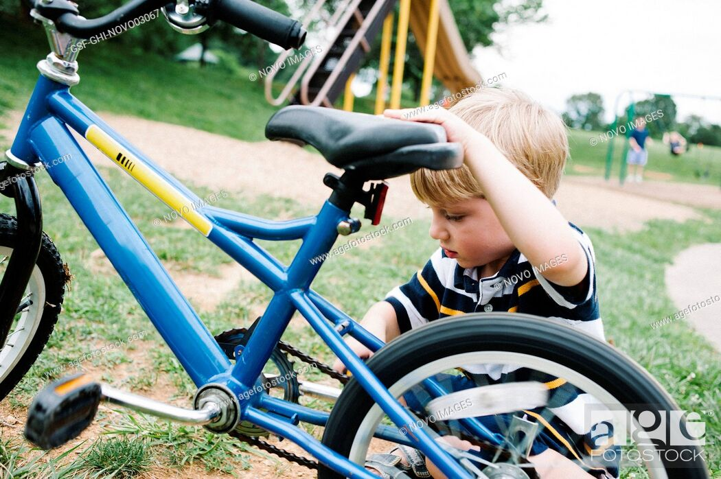 Imagen: Young Boy Working on Bicycle.