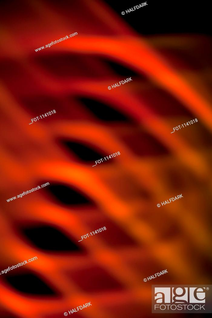 Stock Photo: Abstract pattern of crisscrossing orange and red light beams.