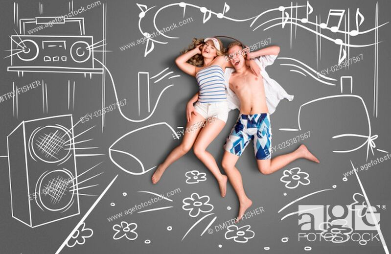 Stock Photo: Love story concept of a romantic couple lying in bed, sharing headphones, and listening to the music against chalk drawings background of a bedroom with.