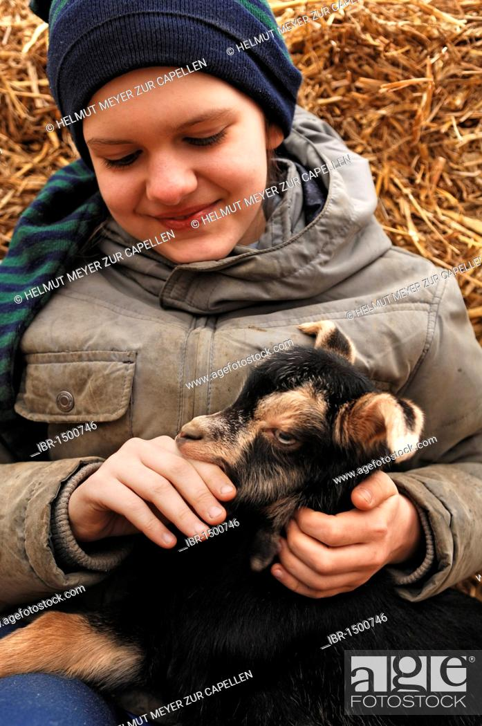 29c4b39dbb6 Stock Photo - Ten-year-old girl sitting on straw embracing a goat kid on an  organic farm