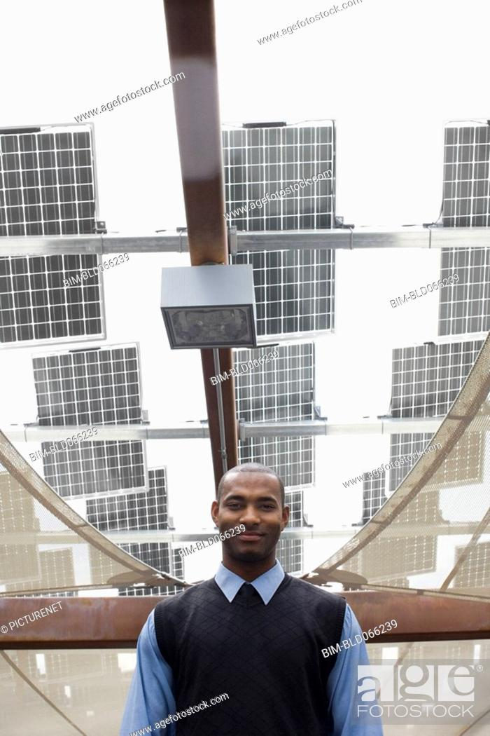 Stock Photo: African businessman standing near solar panels.