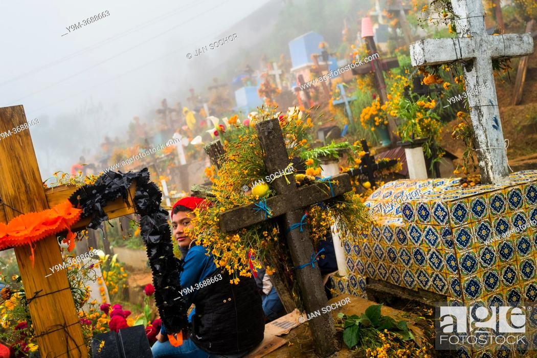 Stock Photo: A Mexican boy sits on a flower-decorated grave at a cemetery during the Day of the Dead celebrations in Ayutla, Mexico, 2 November 2019.