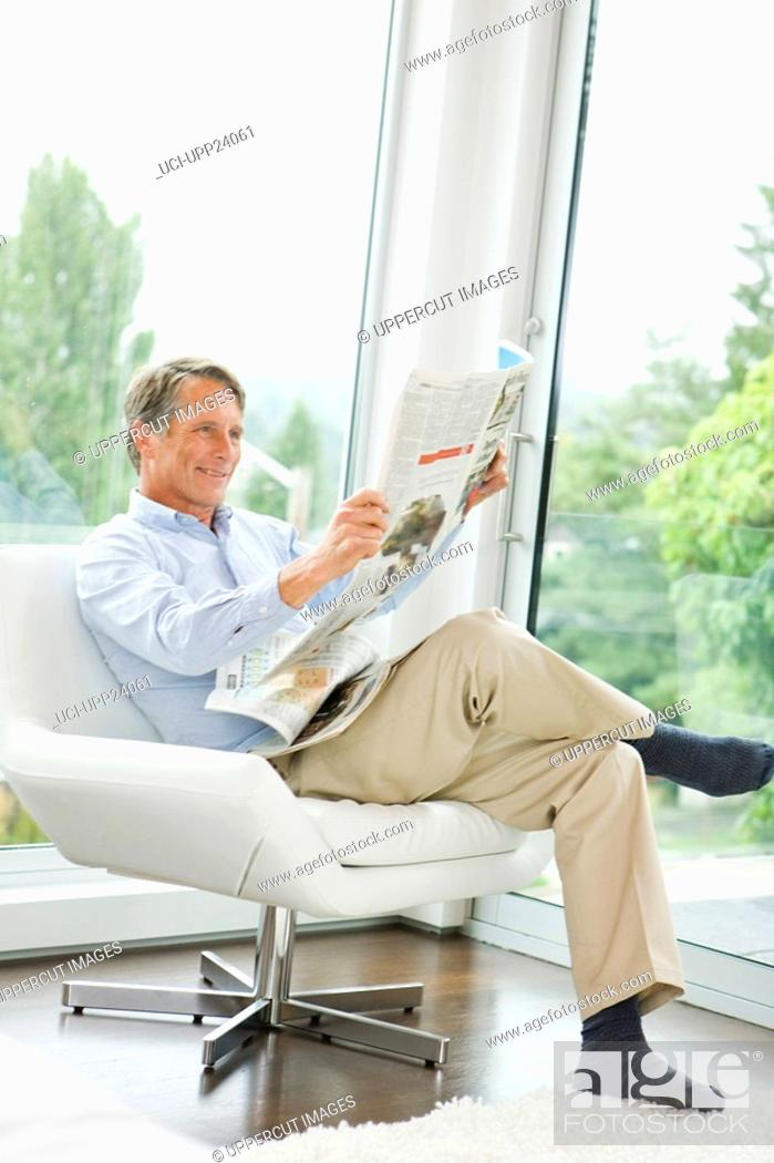 Stock Photo: Man reading newspaper in living room.
